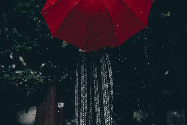 Hold håret tørt med en rød taskeparaply
